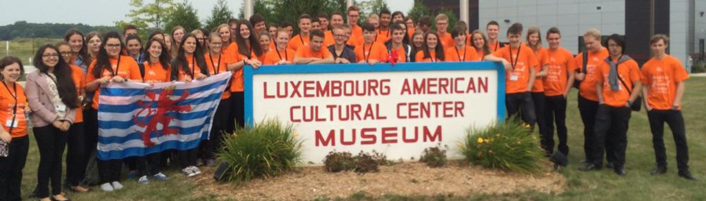 kids in orange t-shirts gathered around LACS sign