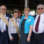 A man and a woman with a tiara wearing gold sashes standing next to another man and woman.
