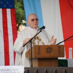 Priest speaking at a podium with a U.S. and Lux flag behind him.