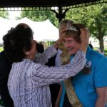 Woman placing a tiara on the head of another woman.