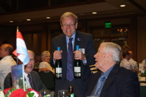 An older man holding up two bottles of white, smiling.