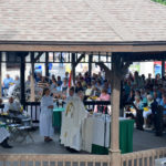 Mass held in a gazebo with a large audience watching.