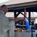 Priest speaking at an alter during an outdoor mass.