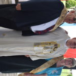 Priest standing between a man and woman who both wear sashes and the woman wears a tiara.