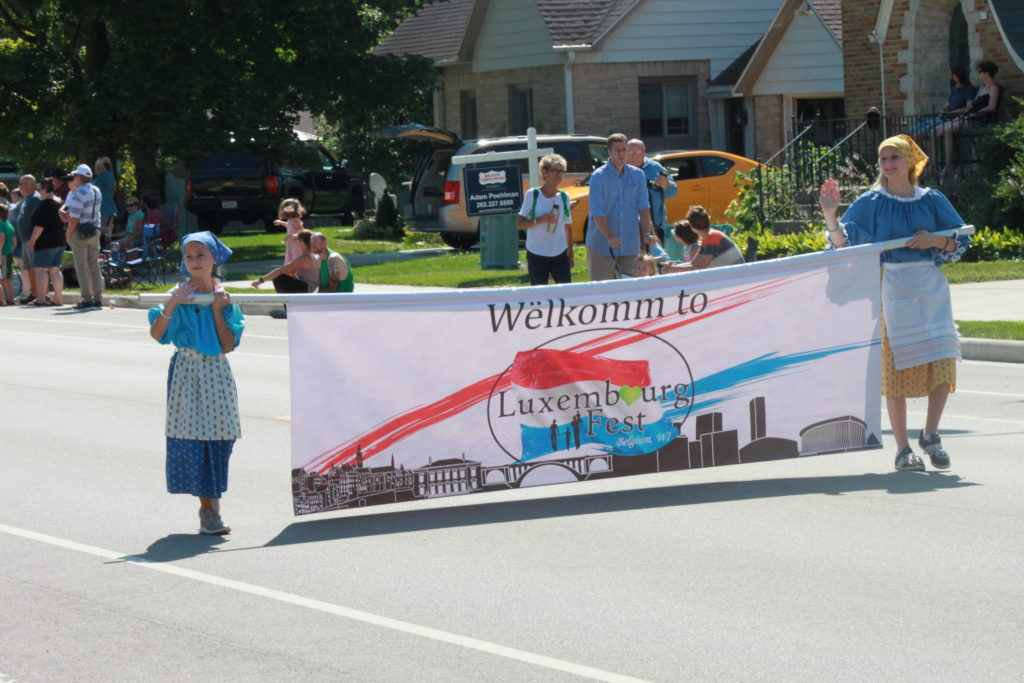 """A woman and a child carrying a banner """"Welkomm to Luxembourg Fest."""""""