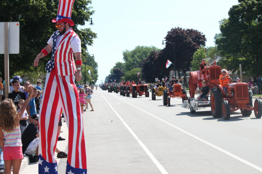 Parade with several tractors, one after another and a man on stilts in US flag clothing.