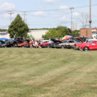 Cars in a car show lines up in a curve.