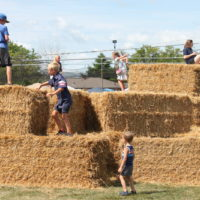Kids playing on bails of hay.