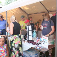 LACS shop tent with people browsing through items.