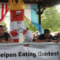 Two men at a table for a Treipen Eating Contest.