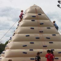 Kids climbing a bouncy pyramid.