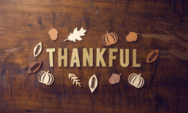"""""""Thankful"""" spelled out on a table with pumpkin and leaves art."""